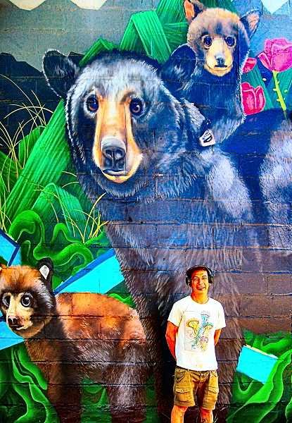 RITA A. LEONARD - Artist Jeremy Nichols stands with the new bear-themed mural he created on the north wall of a business building at the corner of S.E. Yukon Street and Milwaukie Avenue in Westmoreland.