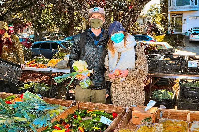 DAVID F. ASHTON - Woodstock Farmers Market shoppers are Steven Boldt and Katie Miner, at the Winters Farms stand.