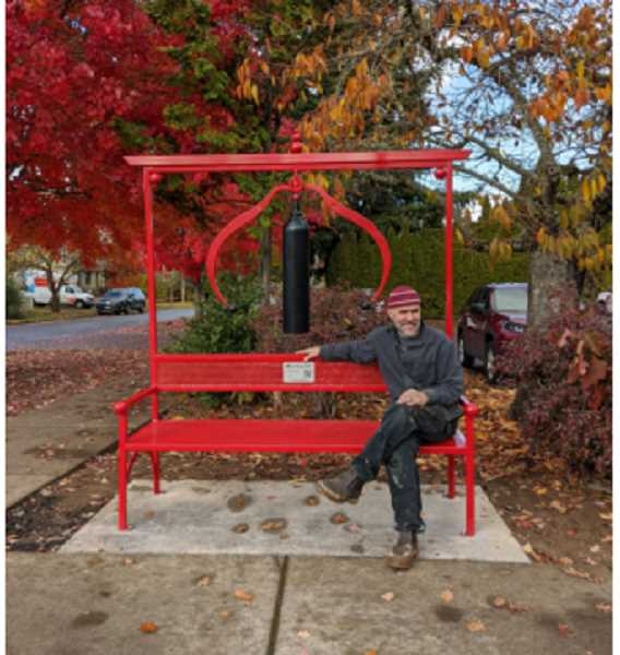 COURTESY PHOTO - Bench designer and creator Jud Turner sits on the bench following its install Friday, Nov. 13, at the corner of 21st Avenue and A Street in downtown Forest Grove.