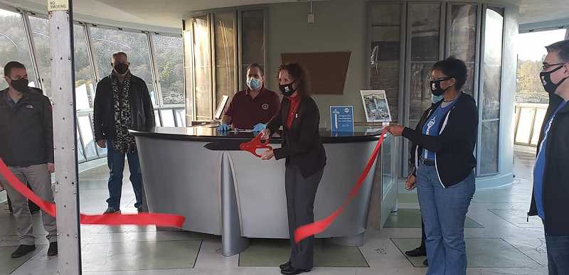 COURTESY PHOTO: TOM GEIL - Oregon City Commission President Rachel Lyles Smith cuts the ribbon for the Municipal Elevator's Tourism Kiosk as Commissioners Rocky Smith and Denyse McGriff (right) look on.