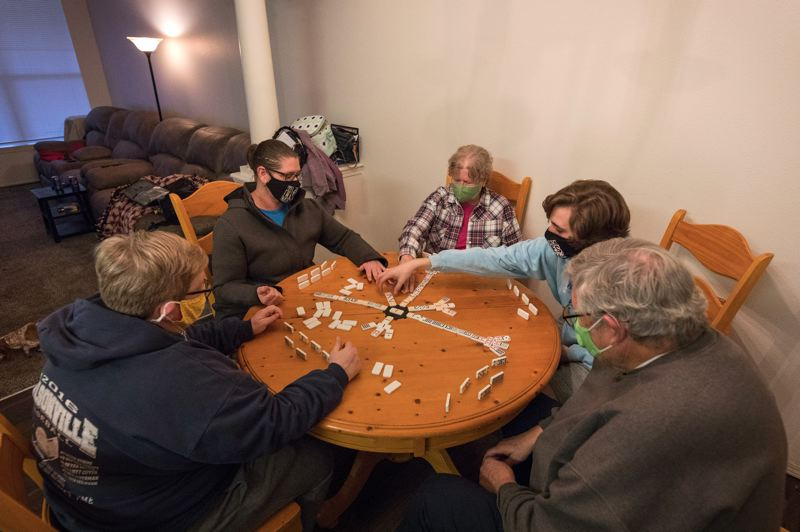 PMG PHOTO: JAIME VALDEZ - Molly Martin,left, Erin Nicks-Martin, Pat Nicks, Gavin Fulbright,19, and Charley Nicks, play a game of Dominoes, a family game favorite.