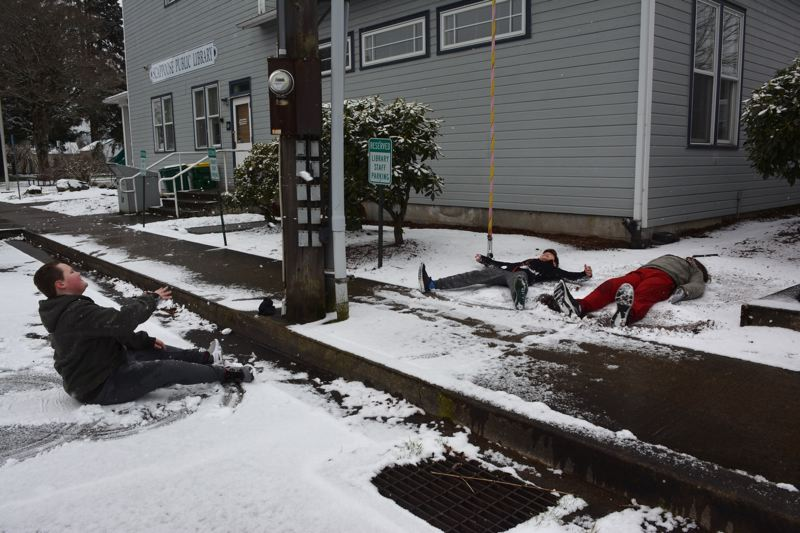 PMG PHOTO: COURTNEY VAUGHN - Scappoose residents Triston, Isaiah and CJ make snow angels and snowballs during a snow day in January 2019.