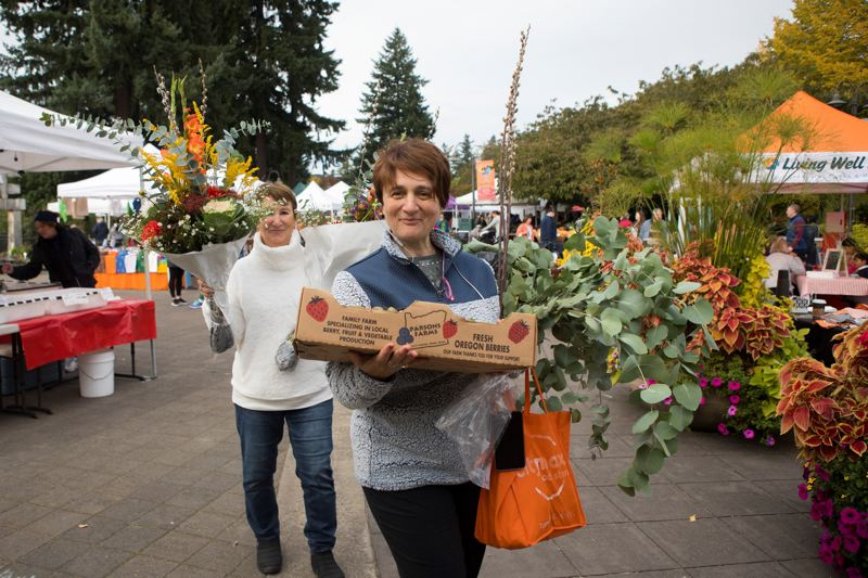 PMG FILE PHOTO - Marina Miller, foreground, and her mom, Irene Rudikov, carry kiwi berries and a bouquet of flowers at last year's Lake Oswego's Farmers' Market.
