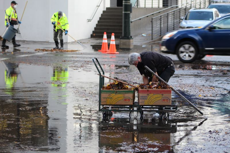 PMG: JOSEPH GALLIVAN - Safeway worker Lar clearing leaves from the drain at Northwest 13th Avenue and Lovejoy Street on Wednesday at dusk.