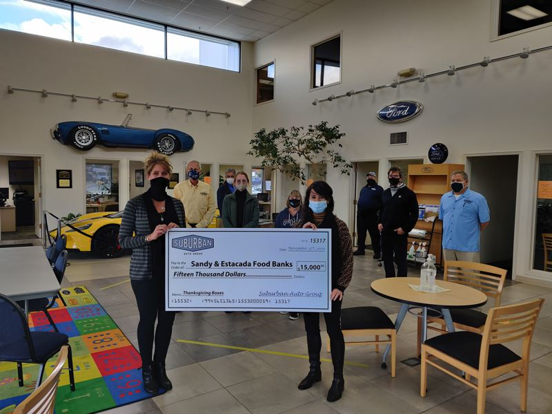 COURTESY PHOTO: SUBURBAN AUTO GROUP - Erinn Sowle of Suburban Auto Group (right) presents check for the Sandy Community Action Center and Estacada Food Bank to Kirsten Pitzer of Sandy Community Action Center (left).
