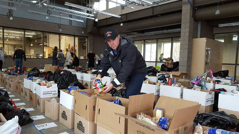 2015 PMG FILE PHOTO - Adopt-a-Family project leader Izaak Thoman, a Gladstone firefighter, loads food boxes that will bring holiday cheer to local families.