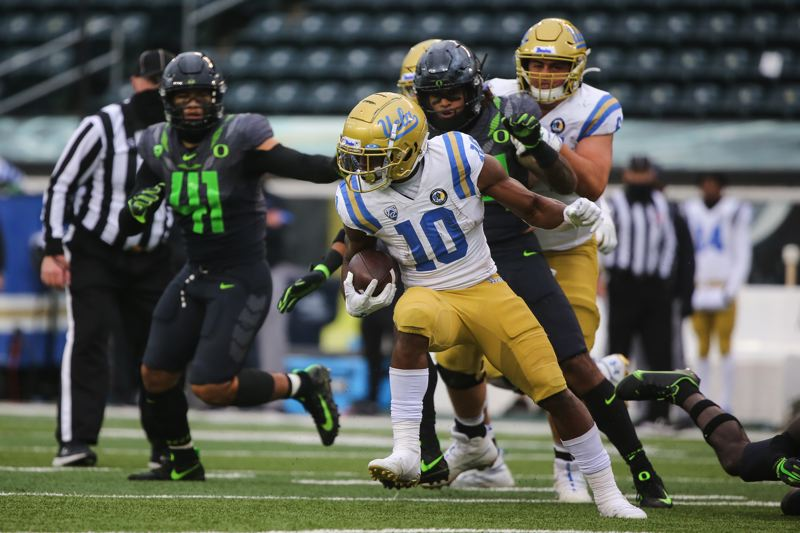 COURTESY PHOTO: ERIC EVANS - For much of Saturday, the the Ducks, including Isaac Slade-Matautia (41) had their hands full containing UCLA's Demetric Felton (10).