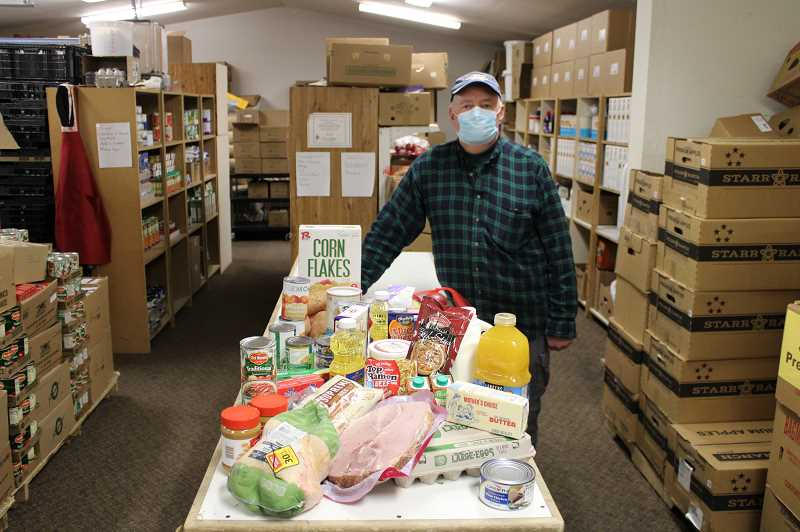 PAT KRUIS/MADRAS PIONEER - Volunteer Mark Carman displays the typical grocery cart available for a family of four at the Jefferson County Food bank. The Food Bank operates out of a building at 556 SE 7th on the campus of the Madras Seventh Day Adventist Church.