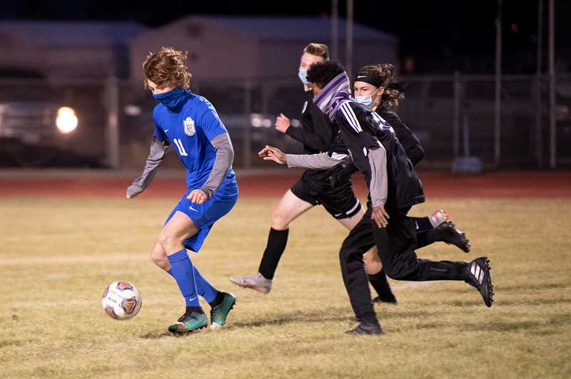 LON AUSTIN - Cainan Smith pushes the ball against Ridgeview on Nov. 17. The Cowboys' effort drew the praise of coach Jonny Oelkers, but the Ravens raced out to a quick 5-0 lead after 10 minutes, then cruised to the 7-1 victory. Adam Ortiz scored the Cowboys' goal.