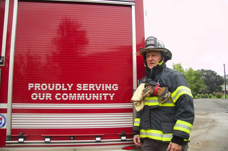 PMG PHOTO: SAM STITES - Steve McAdoo, 17-year veteran engineer with Clackamas Fire District, poses for a photo next to one of the engines parked at Station 15 in Oregon City.