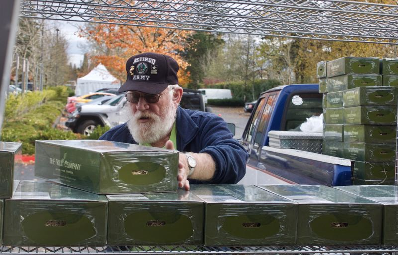 PMG PHOTO: CHRISTOPHER KEIZUR - Whitey Martin, a veteran and member of the American Legion, stacks the food boxes.
