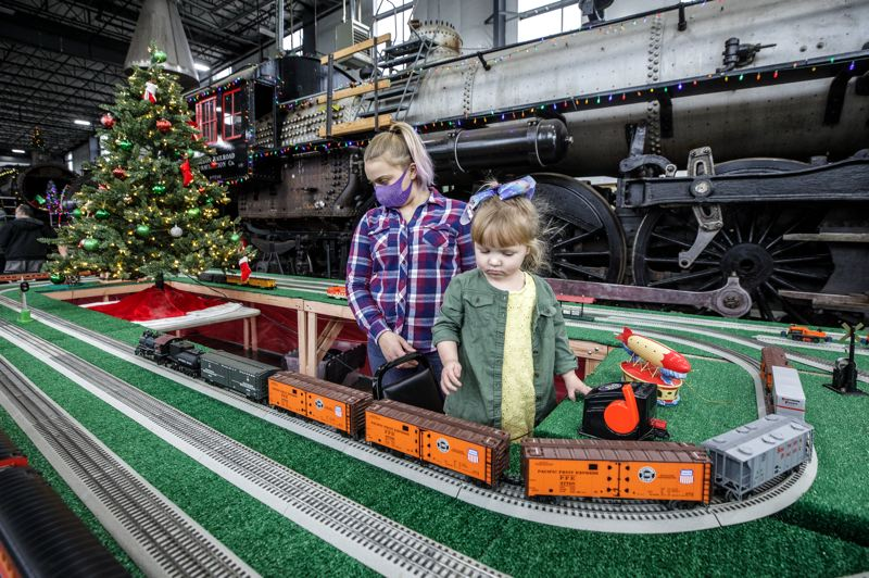 PMG PHOTO: JONATHAN HOUSE - Caitlyn Arendt, center, and Memphis Ingram check out the model trains of the Santa's Enginehouse exhibit at the Oregon Rail Heritage Center.