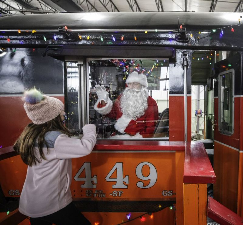 PMG PHOTO: JONATHAN HOUSE - Before the fundraiser was canceled, Santa practiced waving to Stella Pitt behind plexiglass in the cab of the Southern Pacific 4449 at the the Oregon Rail Heritage Center.