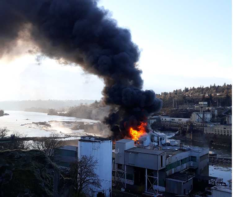 PMG PHOTO: CHRIS SWEET - Willamette Falls can be seen in the background as the shuttered Blue Heron paper mill continues to burn on Dec. 5.