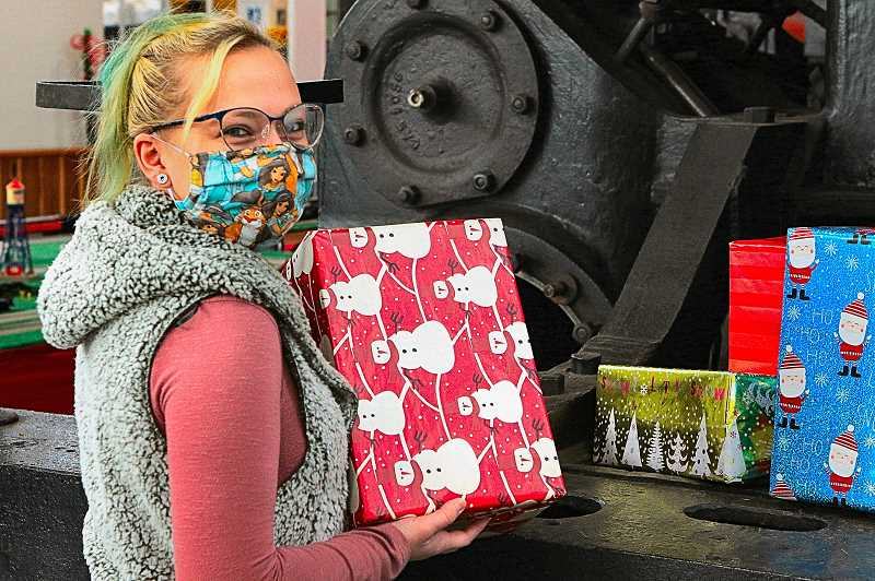 DAVID F. ASHTON - Volunteer Mariah Arendt brought a Holiday gift-wrapped box to a display on the front of a locomotive; since it will now not be open to the public, youll only see it here.