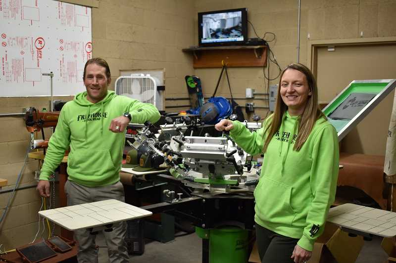 "RAMONA MCCALLISTER - Seth Reno and Amanda Drake stand by their screen printing equipment at their Prineville business. They recently incorporated ""I DID"" into their intellectual property as a TM (Trademark)."