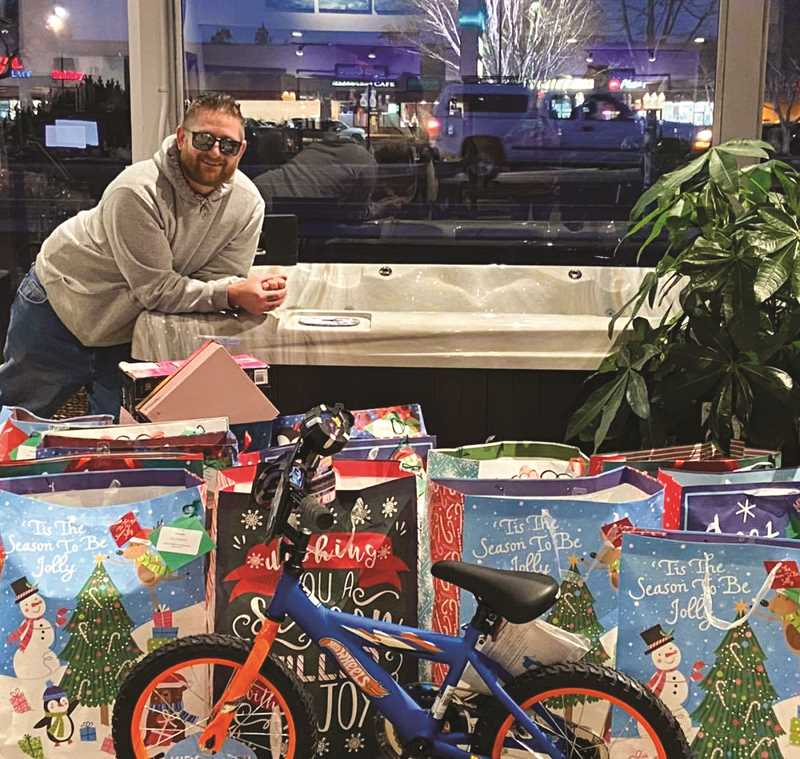 PHOTO COURTESY OF JILLIAN SEAWEARD  - Brandon Tappert stands behind the pile of toys that he bought after taking all the tags off the Tree of Joy at Sunrise Pool and Spa recently. The tree was for children and teens.