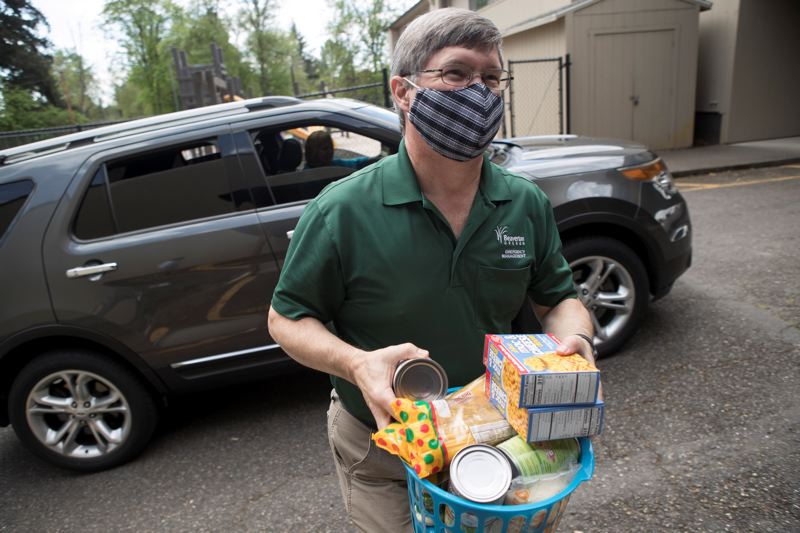 PMG PHOTO: JAIME VALDEZ - Beaverton emergency manager Mike Mumaw carries a basketful of food donated by a person to the food donation center at Village Church in May.
