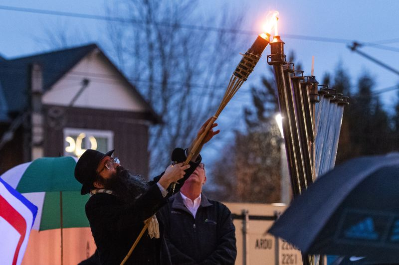 PMG FILE PHOTO: - Rabbi Menachem Rivkin lights the menorah during the Light Up Hillsboro event for the first night of Hanukkah at the Jerry Willey Plaza at Orenco Station in Hillsboro in 2019.