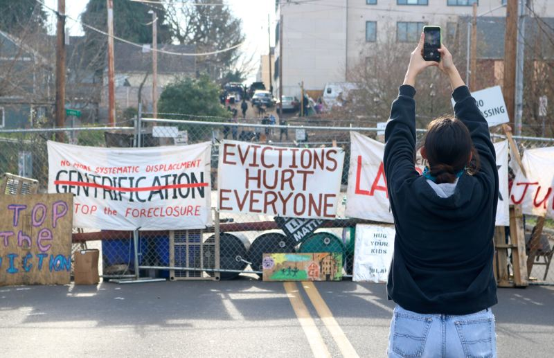 PMG PHOTO: ZANE SPARLING - A barricade at the Red House occupied zone in Portland is draped with a banner reading 'evictions hurt everyone' on Oct. 8.