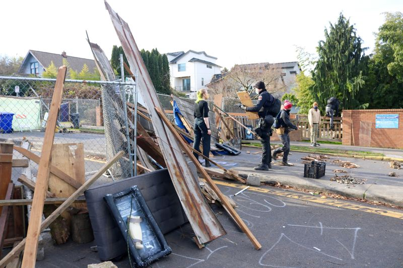 PMG PHOTO: ZANE SPARLING - Black-clad protesters used power tools, spare lumber, trash bins and fencing to block access to the 'Red House' on Mississippi Avenue in North Portland on Oct. 8.