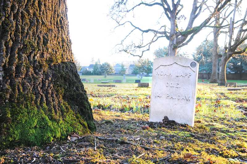 PMG PHOTO: GARY ALLEN - A giant oak tree, damaged during the windstorm on Labor Day, threatened more than a dozen headstones of Civil War veterans before it was taken down on Dec. 4 in Newberg.