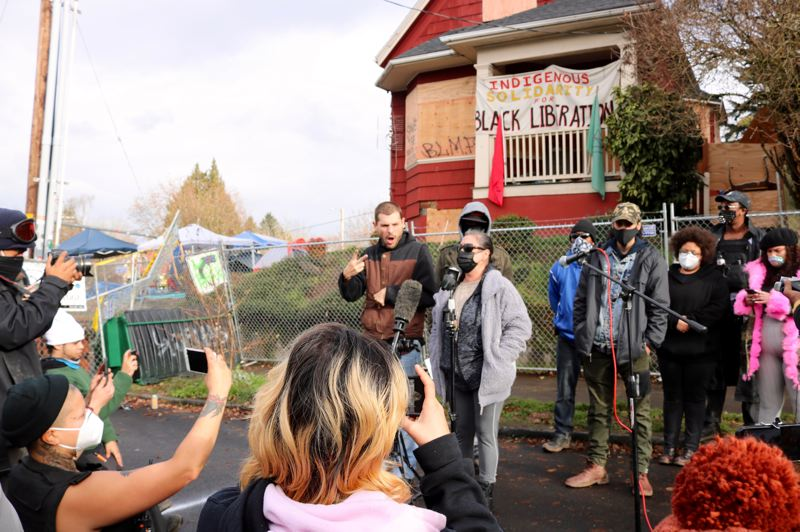 PMG PHOTO: ZANE SPARLING - Julie Metcalf Kinney, at center, speaks at a press conference in North Portland at the Red House on Mississippi Avenue on Wednesday, Dec. 9.