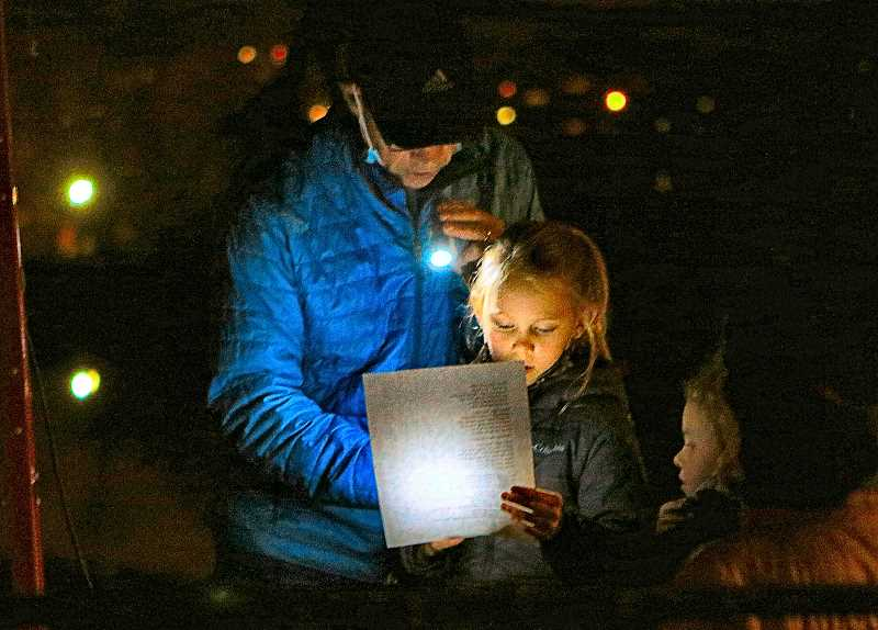 DAVID F. ASHTON - Matt Hainley held a flashlight while young Cora Lax led the group of spectators singing carols at the SMILE Christmas Tree lighting on Oaks Bottom Bluff, on the evening of Thanksgiving Day.