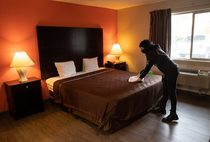 COURTESY PHOTO: JOHS - A service provider clreans and sets up a room at the newest motel provided as COVID-19 housing by the City/County JOINT Office of Homeles Services.