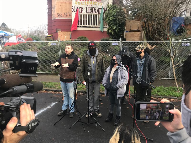 PMG PHOTO: ZANE SPARLING - William Kinney III, at center, who uses the name William X. Nietzche, speaks with reporters during a press conference outside the Red House on Wednesday, Dec. 9. P