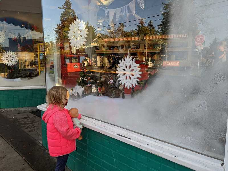 PMG PHOTO: COURTNEY VAUGHN - Eloise, 5, peers in the window of Thinker Toys in Multnomah Village. Thinker Toys reported sales on-par or better than the prior holiday shopping season.