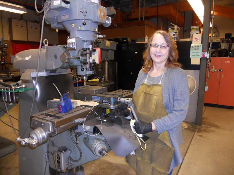 PMG PHOTO: SCOTT KEITH - St. Helens High School teacher Bonnie Adams in front a mill, a tool in manufacturing.