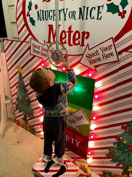 COURTESY PHOTO: KIM REYNOLDS - A youngster shouts into the naughty and nice machine at Santas Christmas Cottage in Old Town Sherwood.