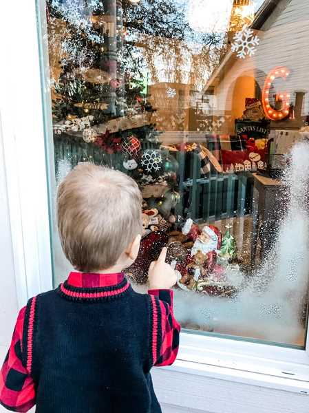 COURTESY PHOTO: KAITLIN CHRISTENSEN - A little boy peers into Santa's lifesized snowglobe as part of Santas Front Porch Experience at Santas Christmas Cottage in Old Town Sherwood.