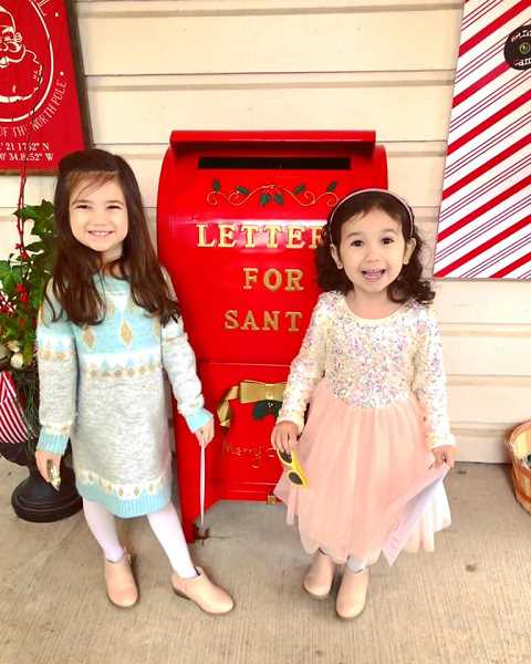 COURTESY PHOTO: RAVEN BORGES - Two girls pose in front of Santas big red mailbox on the porch of Gardner Team Real Estate.