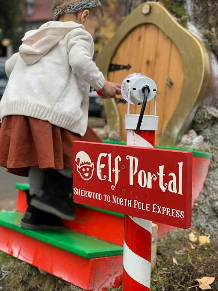 COURTESY PHOTO: TARYN BUTTERFIELD - A child appears into an elf portal that was placed inside a tree outside Santas Christmas Cottage in Old Town Sherwood.
