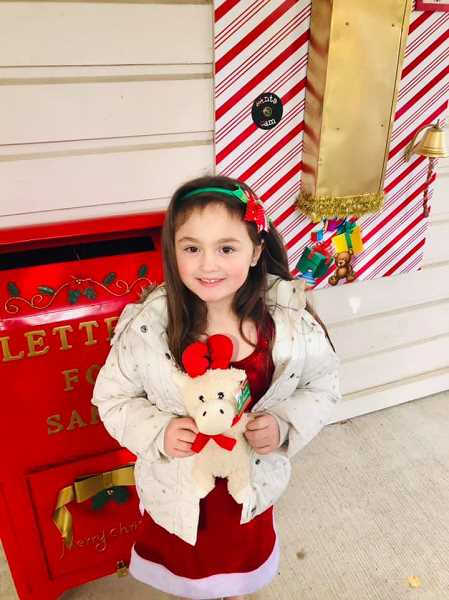 COURTESY PHOTO: LINDSAY CHAQUETTE  -  A child receives a surprise from the toy chute, at right, which is connected to the elves' workshop in the North Pole, according to Amber Gardner, co-owner of Gardner Team Real Estate.