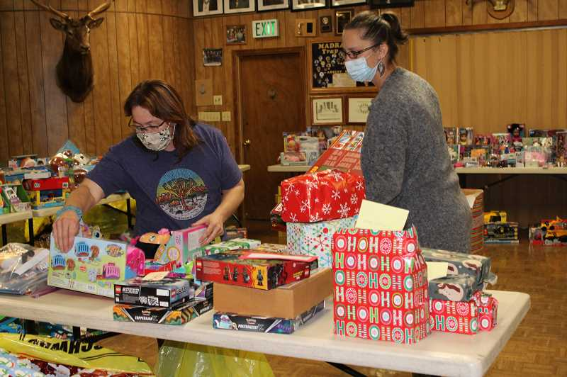 HOLLY SCHOLZ/MADRAS PIONEER - Kim Schmith, left, and Amber Searcy check out some of the presents that Operation Rudolph will be distributing to Jefferson County youth this Christmas.