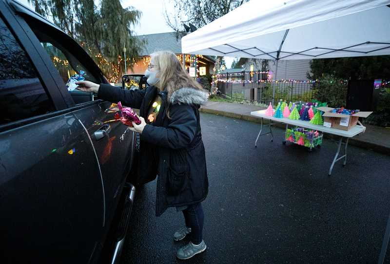 PMG PHOTO: JONATHAN HOUSE - Heidi MacLaren hands out holiday gifts during a drive-thru event at Arts and Technology High in Wilsonville.