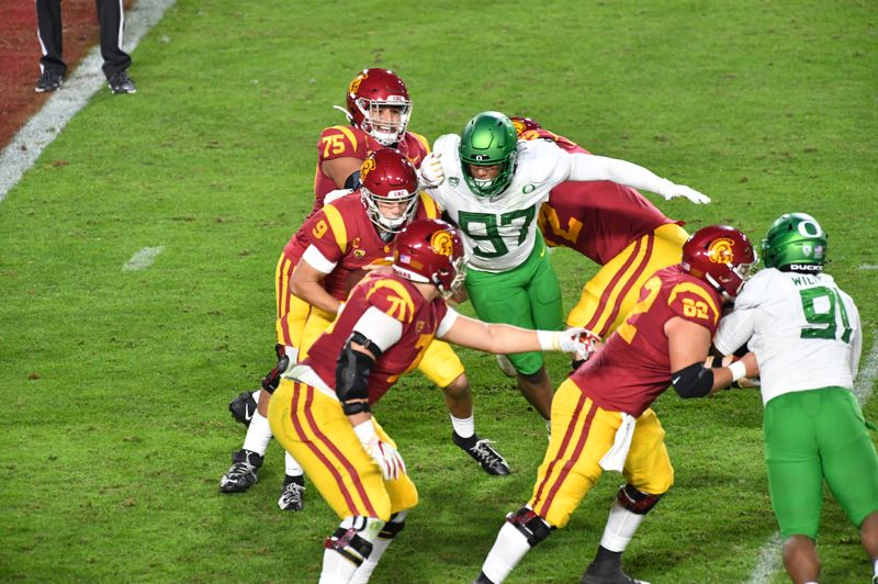 COURTESY PHOTO: DENNIS HAMMOND/LONG PHOTOGRAPHY - Brandon Dorlus (97) closes in on USC quarterback Kedon Slovis during the second quarter of Friday's Pac-12 championship game.