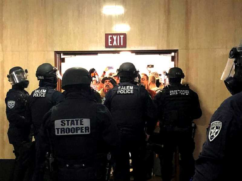 COURTESY PHOTO: DIRK VANDERHART, OPB - State police block an entryway to the Oregon Capitol on Monday, Dec. 21, as far-right protesters attempt to gain access during a one-day special session of the Legislature.