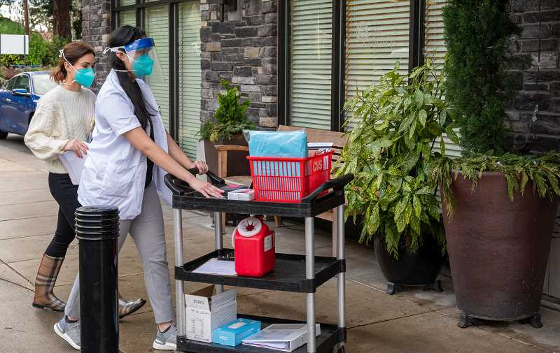COURTESY PHOTO - CVS staff members move equipment to prepare for a vaccine clinic at Rose Villa.