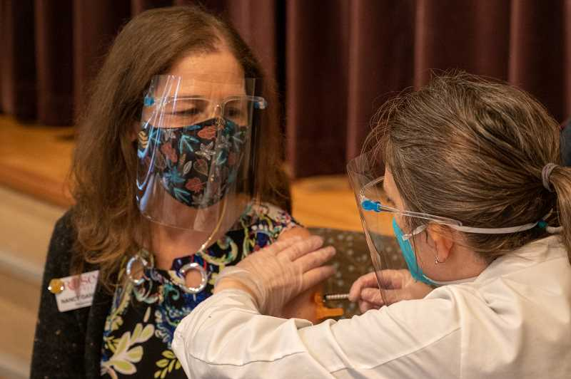 COURTESY PHOTO - Rose Villa staff member Nancy Daniels receives a vaccine against COVID-19 at the Oak Grove senior-living facility.