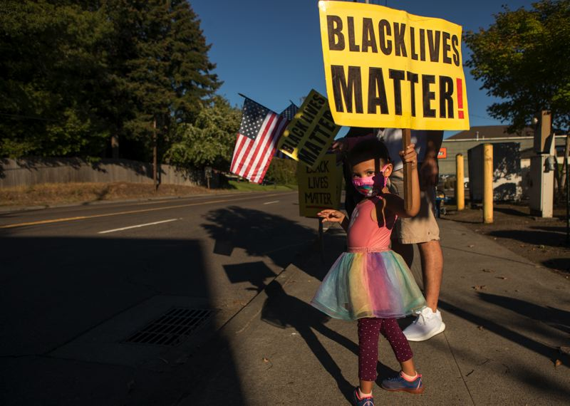 PMG PHOTO: JAIME VALDEZ - A child holds a Black Lives Matter sign during a vigil in Raleigh Hills following the death of George Floyd.
