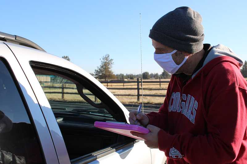 PAT KRUIS/MADRAS PIONEER  - Jefferson County Public Health Director Michael Baker questions a Crooked River Ranch resident during a drive-thru COVID testing and flu shot clinic.
