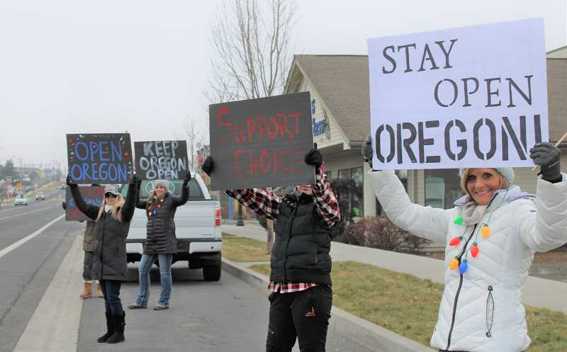 PAT KRUIS/MADRAS PIONEER  - About a dozen protestors showed their support for businesses suffering under COVID restrictions in early December. Organizers of Open Oregon say the state overreached its authority be restricting businesses to curb the spread of the coronavirus. Brenda Williams, far right, wants small businesses to know the group supports their right to stay open.