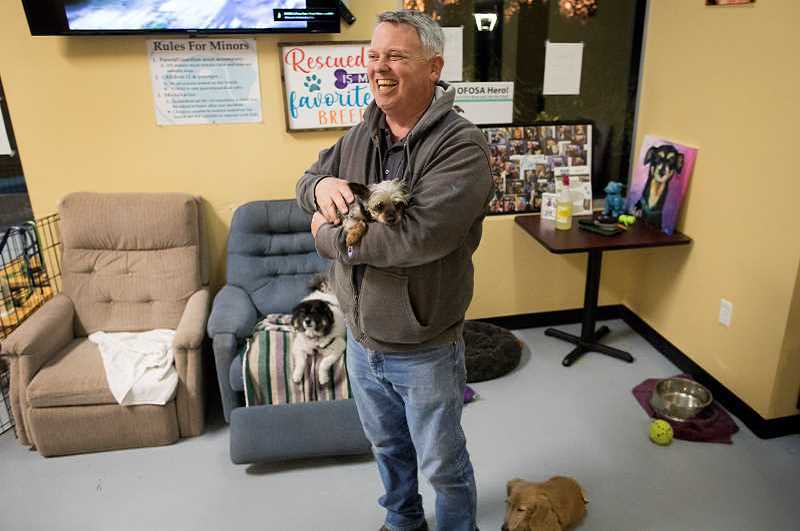FILE PHOTO: JAIME VALDEZ - Scott Porter, owner of Fidos Tap House in Tigard, holds his Yorkie purebred, Meesha, during an interview last year. Money.com recently highlighted Porters business, where residents can grab a beer and adopt a dog, as one of the reasons the city is so dog friendly.