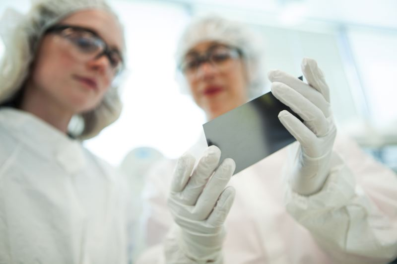 COURTESY PHOTO: TWIST BIOSCIENCE - Two Twist Bioscience employees hold up a sillicon chip the company uses for DNA synthesizing.