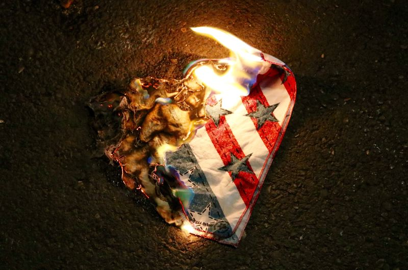PMG PHOTO: ZANE SPARLING - A flag burns in downtown Portland during a protest.