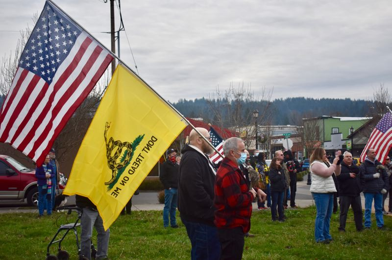 PMG PHOTO: EMILY LINDSTRAND - Multiple flags could be seen at an Open Oregon rally in Estacada on Tuesday, Dec. 29.